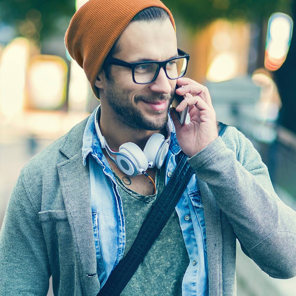 22 college student discounts & freebies – man talking on his phone and smiling