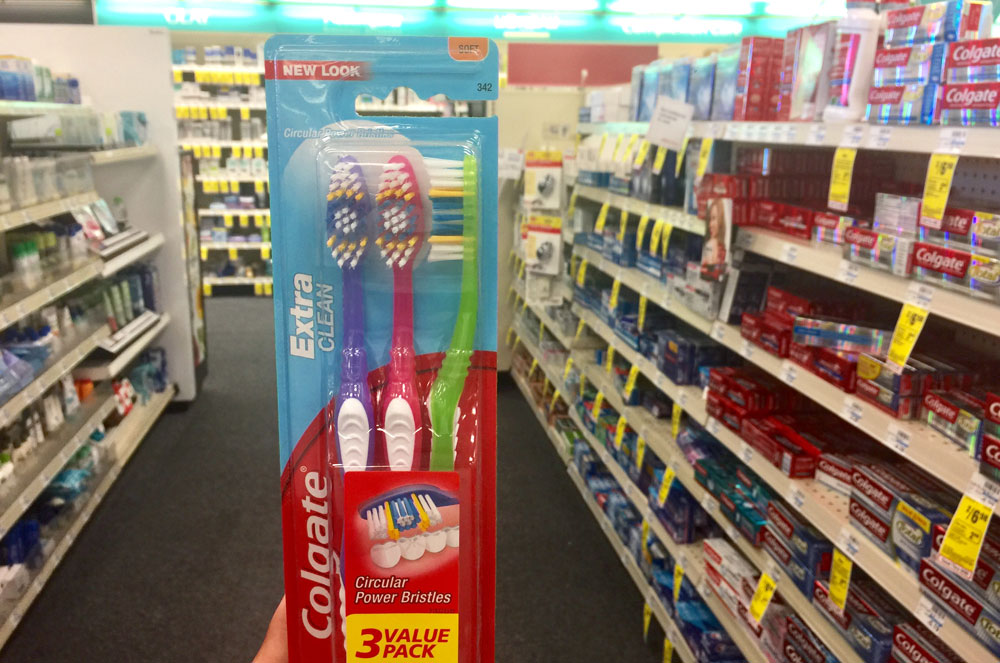 hand holding Colgate toothbrush multipack