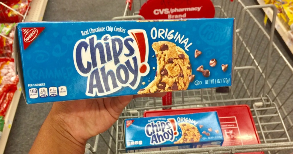 hand holding chocolate chips ahoy! cookies in store above a shopping cart