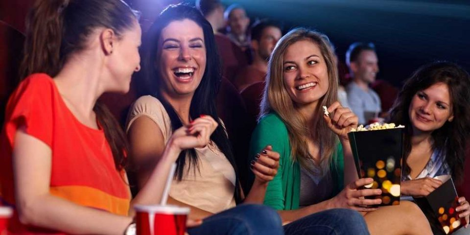 women laughing and talking at the movies