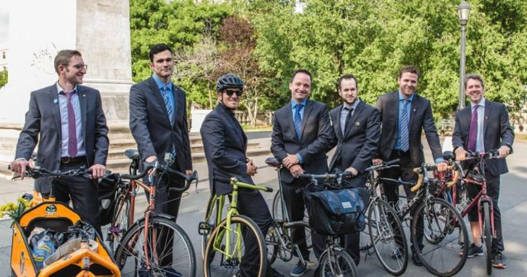 Men wearing suits on bikes
