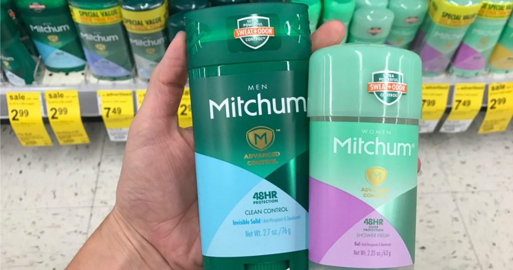 hand holding two Mitchum deodorant