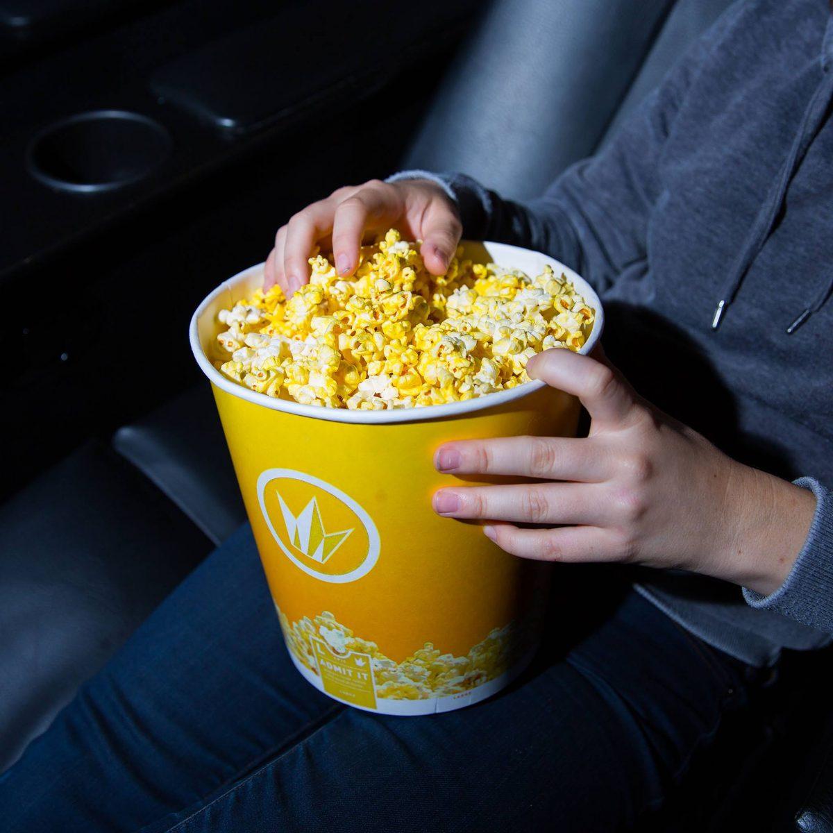 a moviegoer holding popcorn