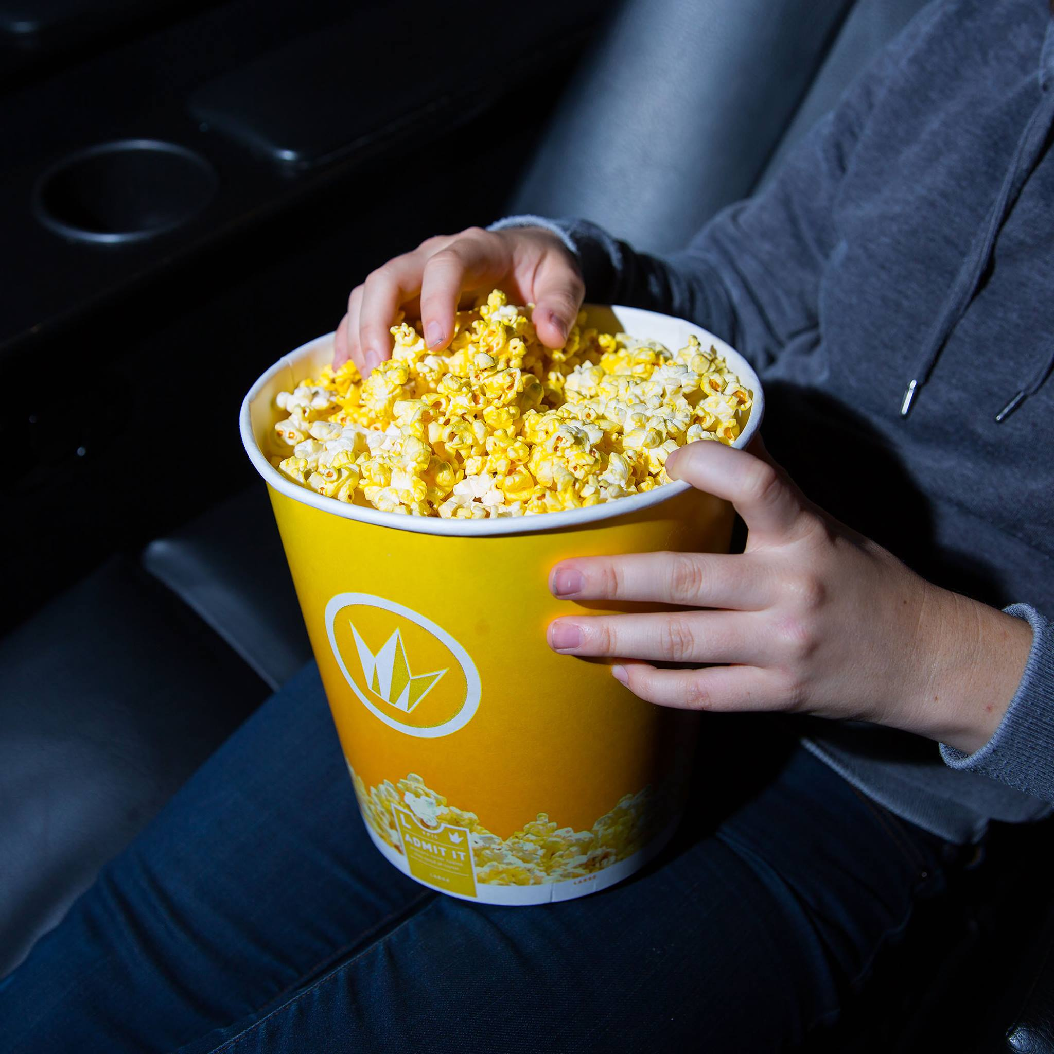 22 college student discounts & freebies – a moviegoer holding popcorn