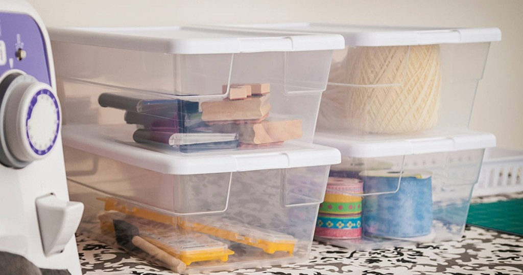 four clear small storage bins with white lids filled with art supplies