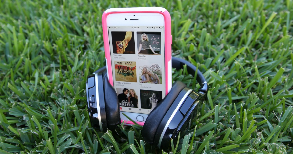cell phone and headphones in grass with apple music opened up on phone