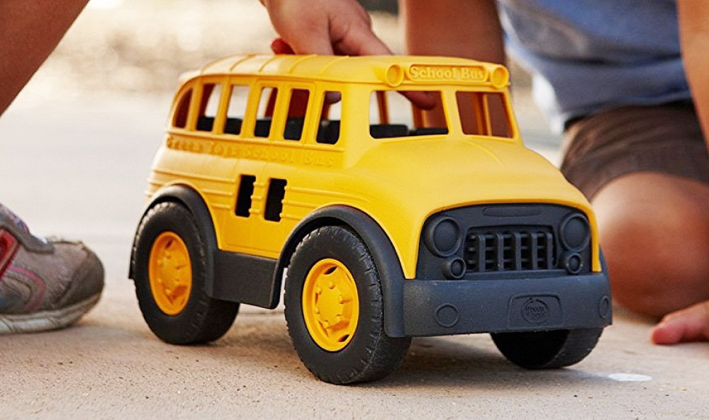 kids playing with a big plastic bus toy