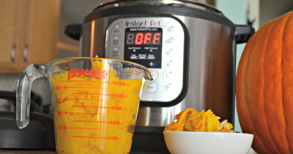 pumpkin puree in measuring cup next to an Instant Pot