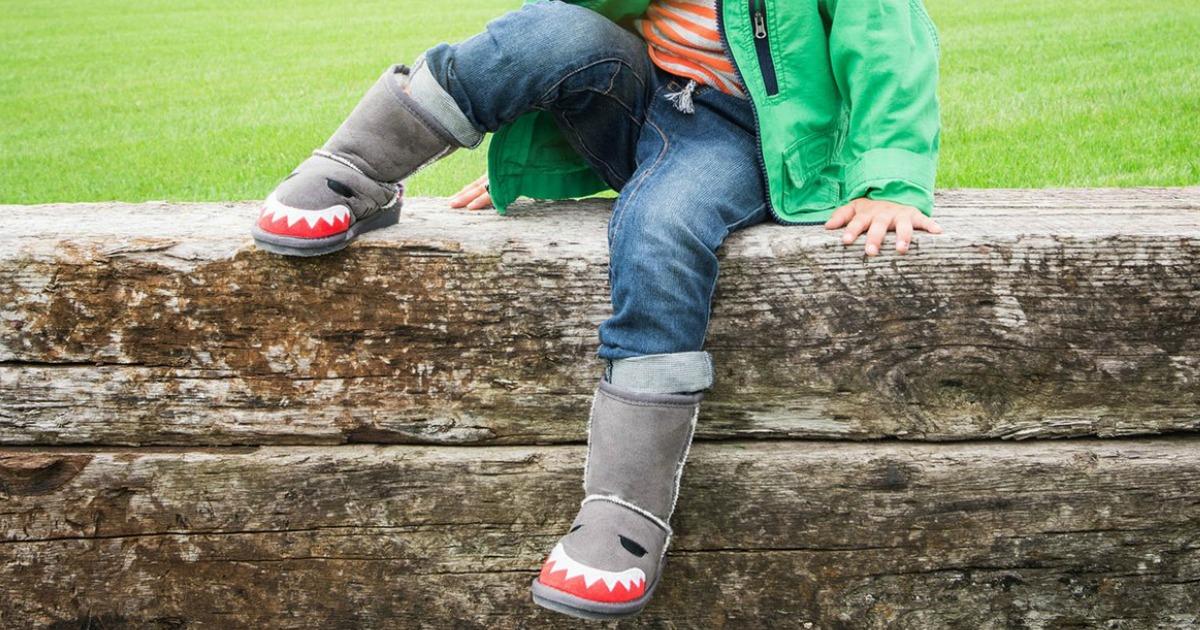 little child wearing a pair of Muk Luk Shark Kids Boots while sitting on logs near grass