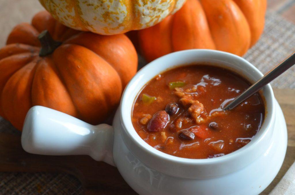bowl of pumpkin chili next to mini pumpkins