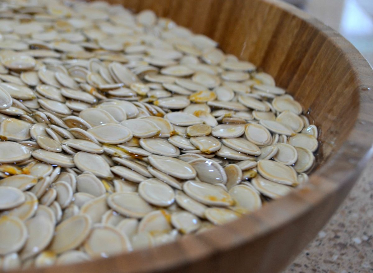 pumpkin seeds soaking in a bowl of water