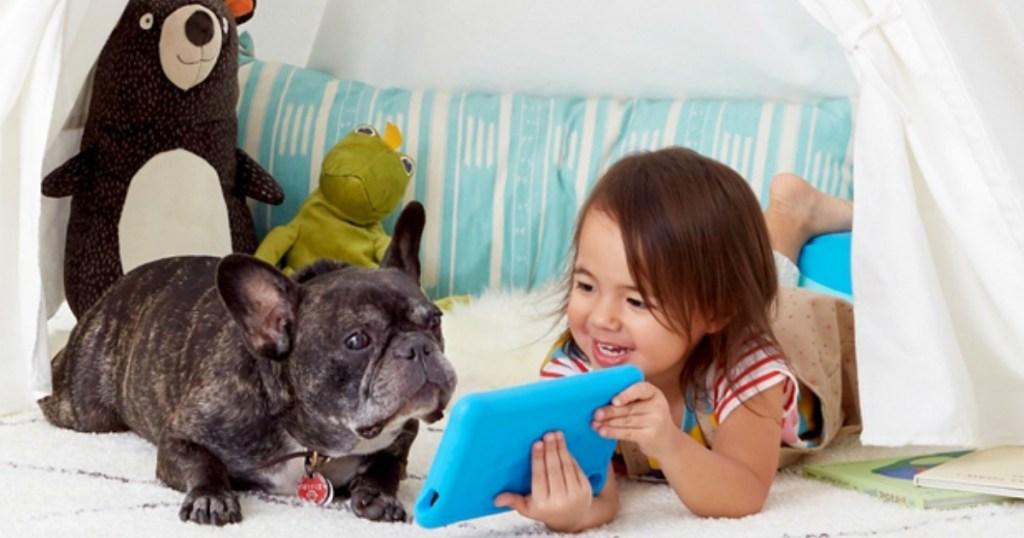 little girl showing her bulldog her blue kindle fire tablet