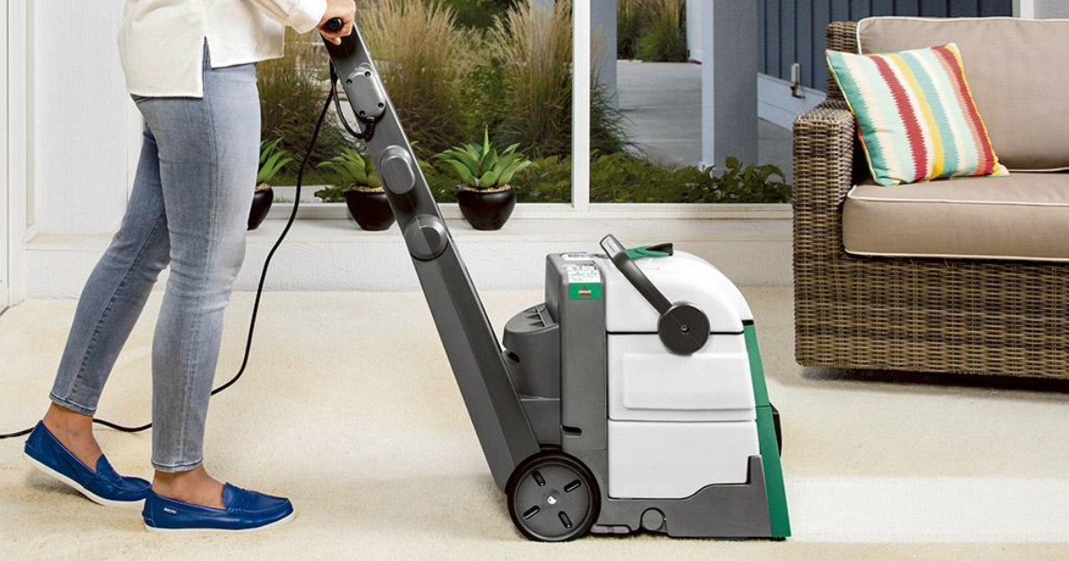 side view of woman cleaning carpet with bissell big green machine
