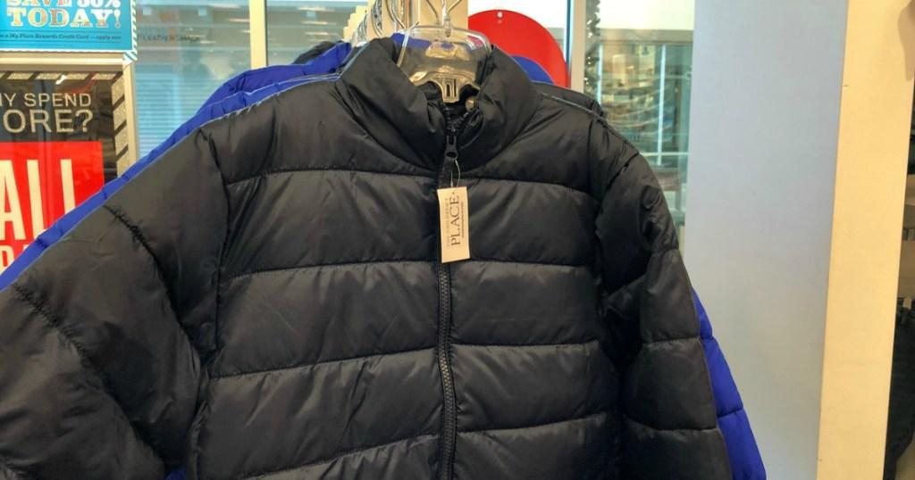 black puffer coat hanging in sore