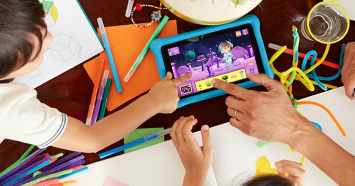 kids and parent using the amazon fire tablet with arts and craft things around it