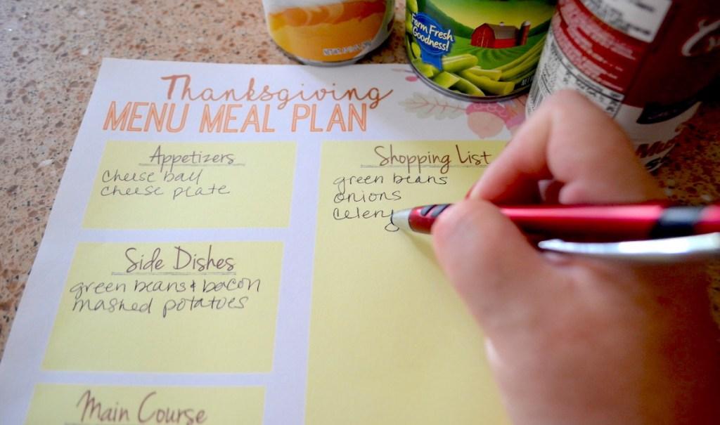 hand holding pen on thanksgiving printable sheet