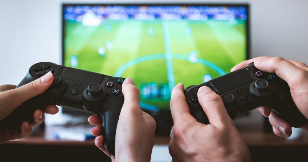 holding video game remotes playing video games