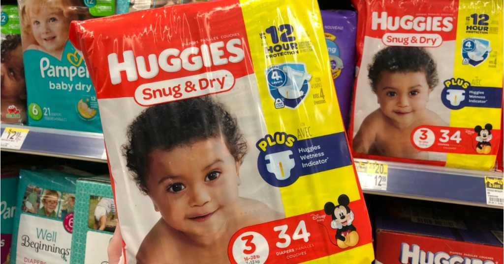 hand holding a package of Huggies diapers