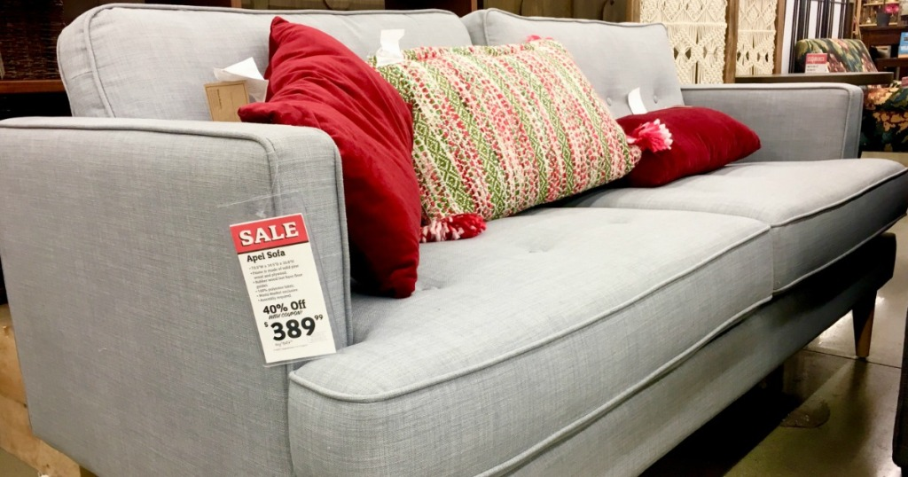 gray couch with red throw pillows and sale tag in store
