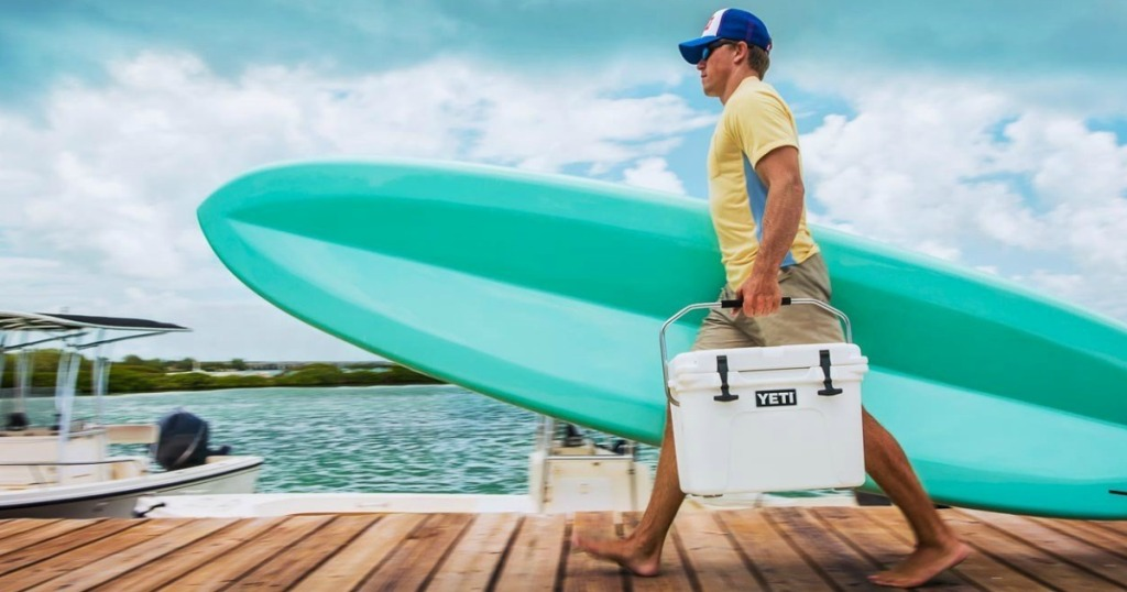 man carrying cooler and surf board