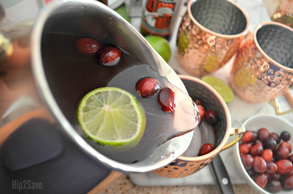 make cranberry moscow mules for a crowd with this easy holiday punch recipe – pouring from the carafe into cups