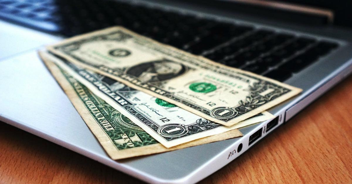 dollar bills on an open laptop