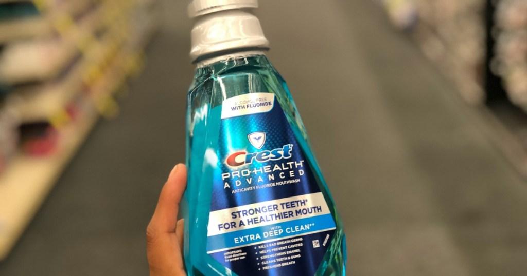 hand holding a bottle of Crest mouthwash