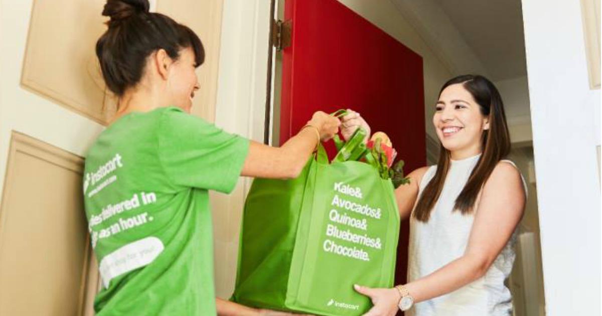 Instacart shopper handing bag of groceries to lady with red front door