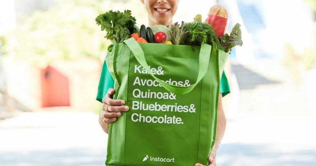 woman holding a reusable instacart shopping bag