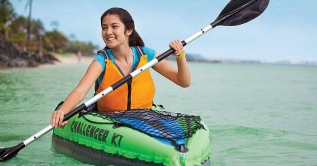 person in green kayak on lake smiling