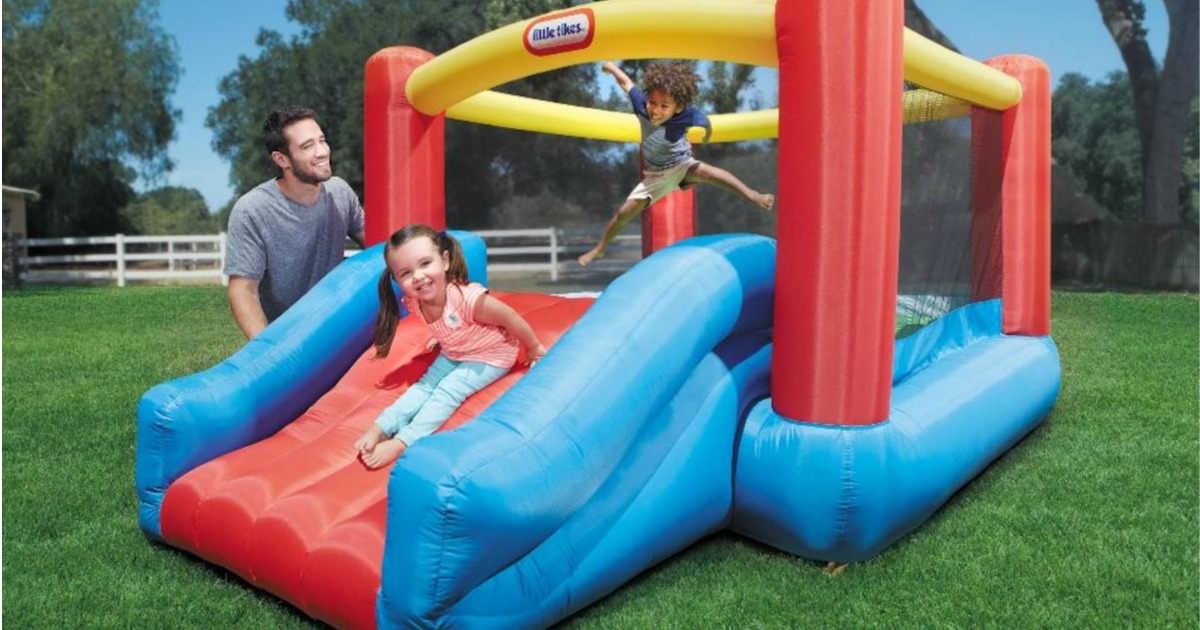 Family outdoors playing on an inflatable bounce house