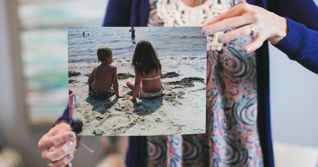 woman holding 8x10 photo print of kids at the beach