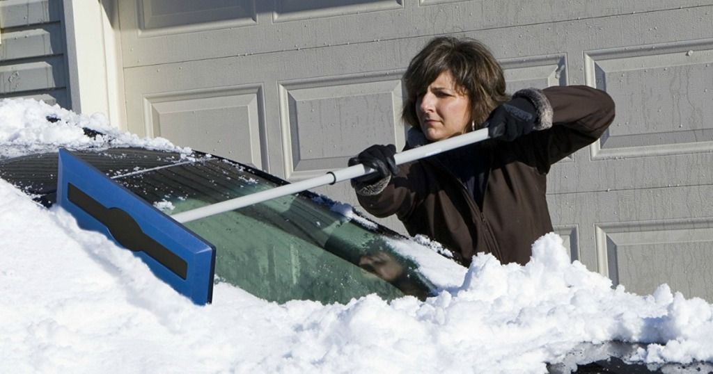 woman shoveling snow off her car