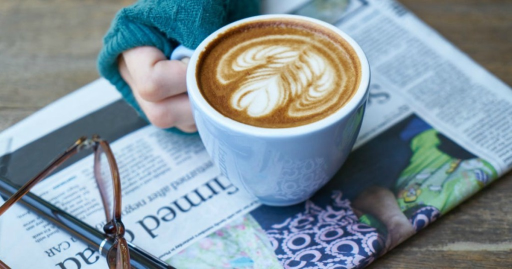 hand holding coffee on newspaper