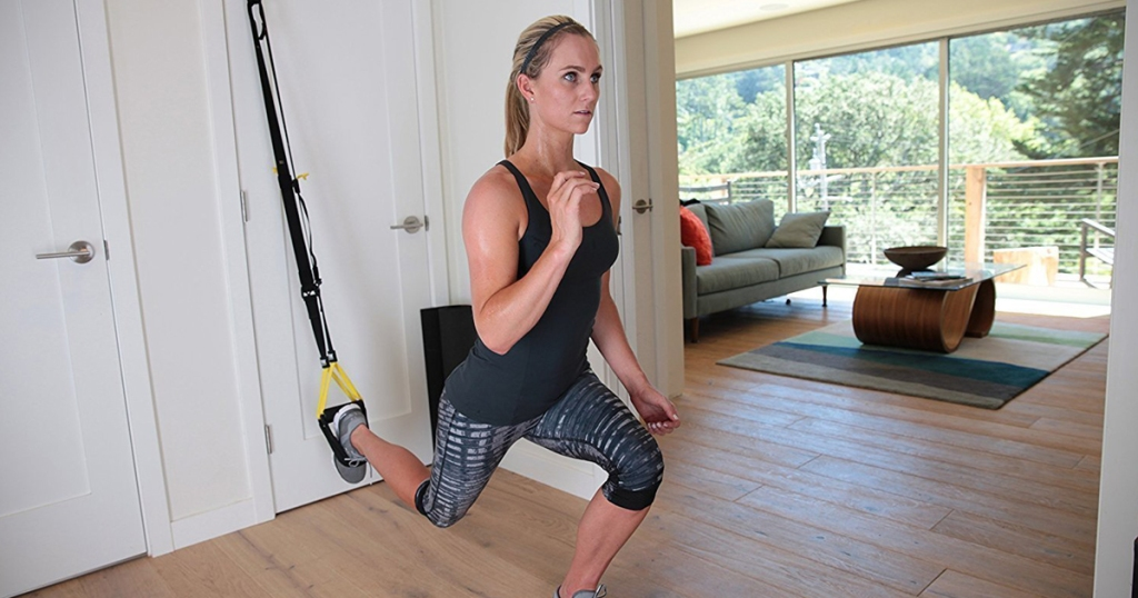 woman using the TRX All-In-One Suspension Training: Bodyweight Resistance System in her home