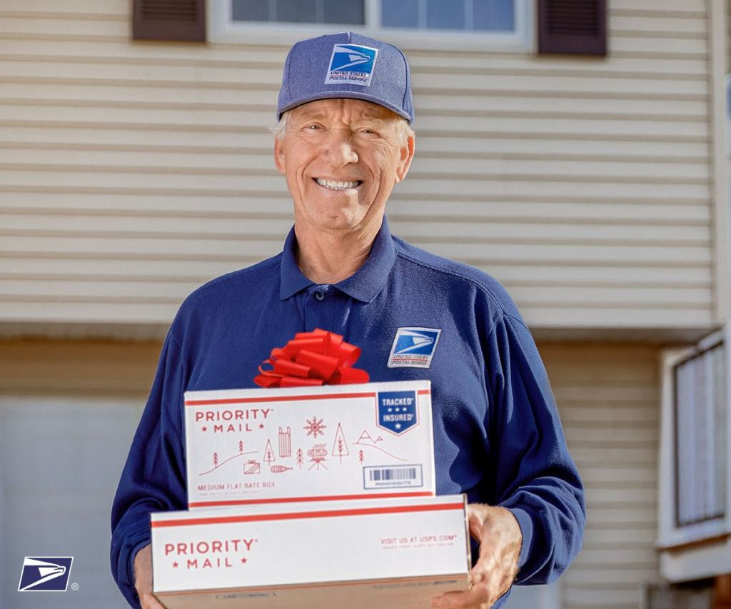 mailman holding priority mail flat rate boxes
