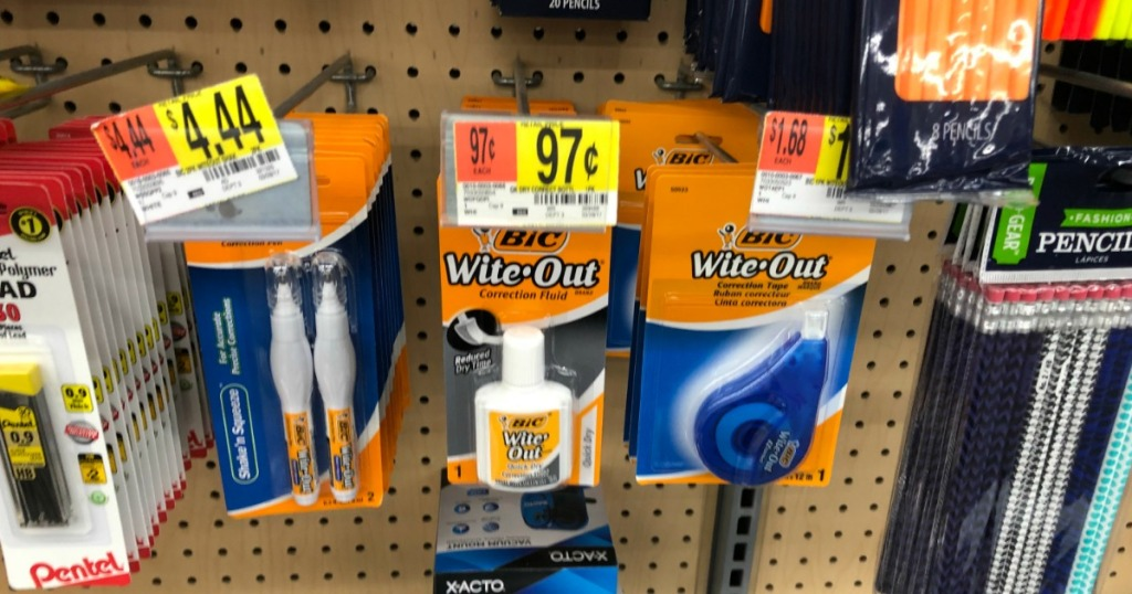 store shelf of office products hanging on peg board with white out packages hanging on the pegs