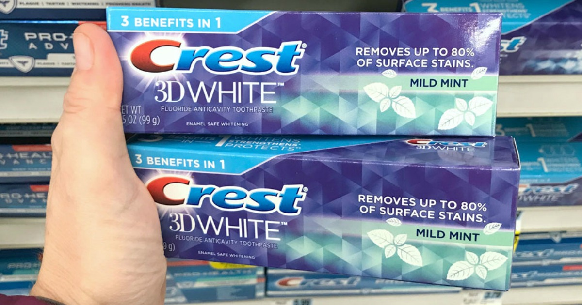 hand holding two boxes of Crest 3D White toothpaste in front of store shelf