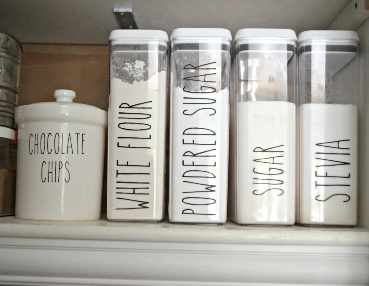 row of plastic containers with baking goods and black lettering on outside