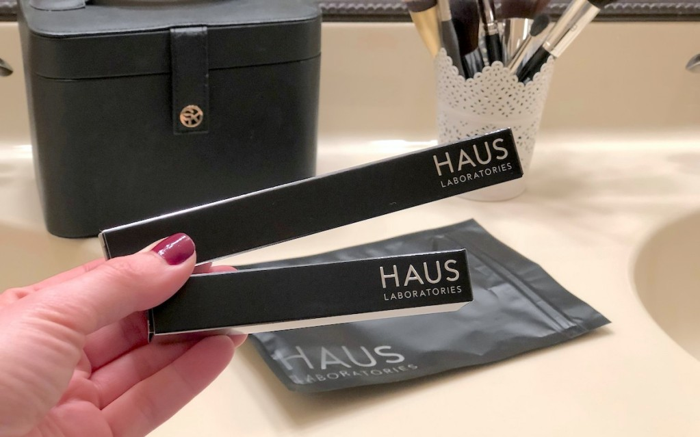 hand holding two black haus laboratories makeup products with bag and brushes in background