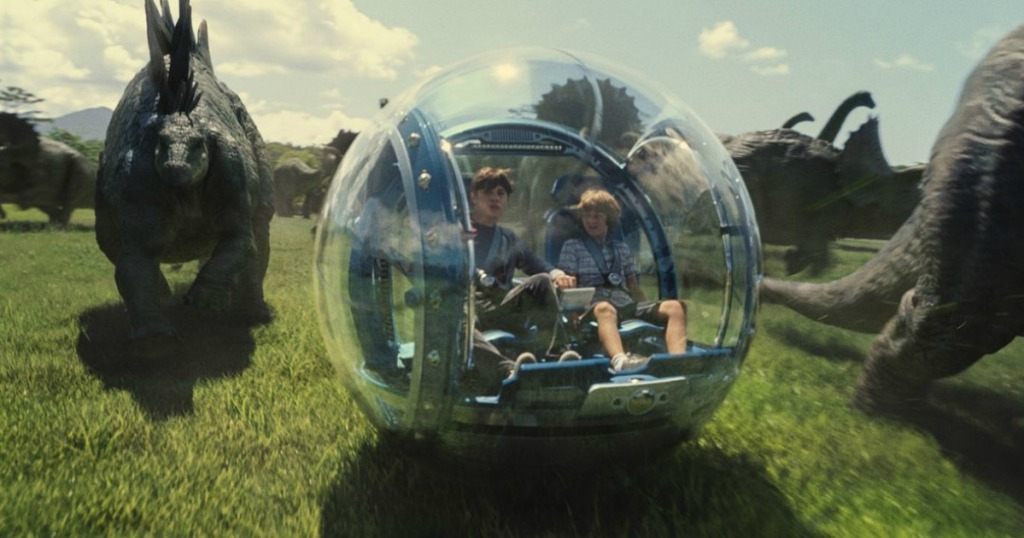 Jurassic World scene of kids riding glass ball ride and dinosaurs in background