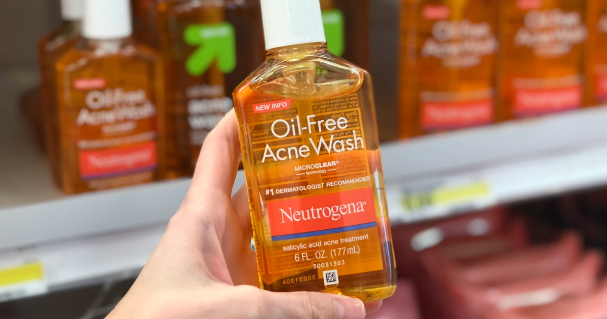 hand holding a bottle of neutrogena acne wash in front of a store shelf