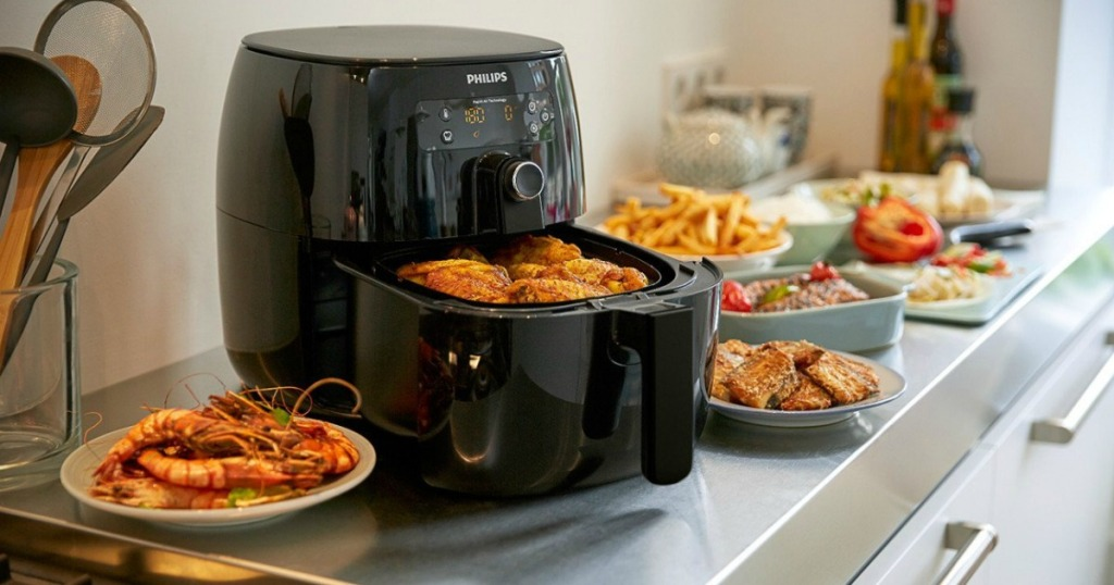 basket pulled partially out of Philips air fryer with fried foods all around