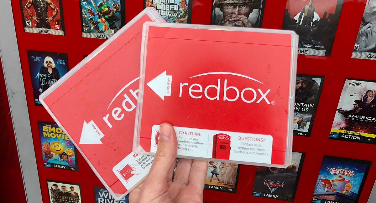 a hand holding two Redbox movie cases outside of the Redbox kiosk