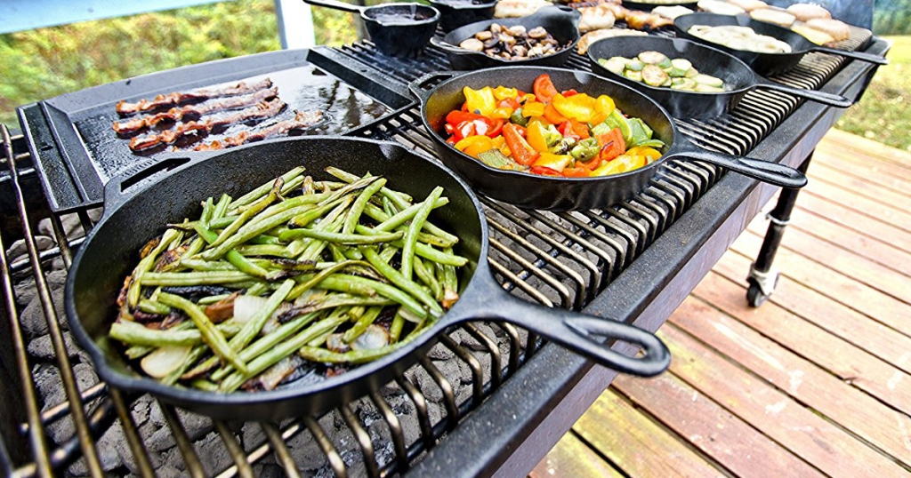 lodge cast iron skillets on big outdoor grill with green beans