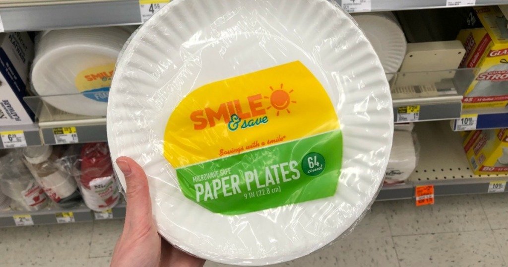 hand holding white paper plates