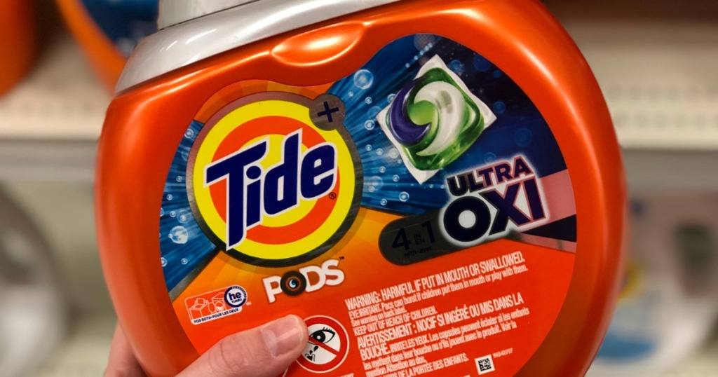 hand holding tide pods ultra oxi with blurred background