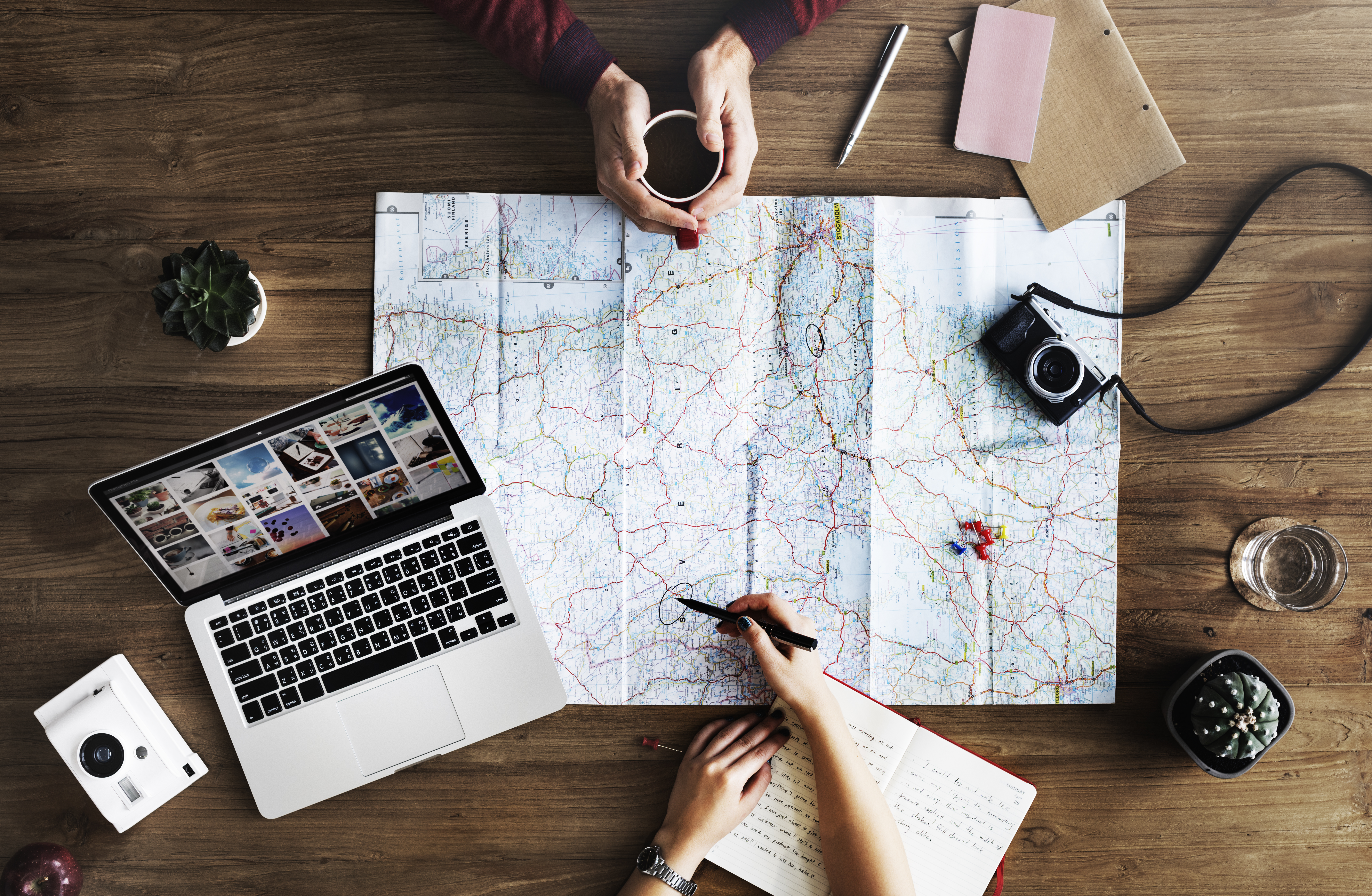 Vacation budget hacks to book the best deals — trip planning around a map and laptop