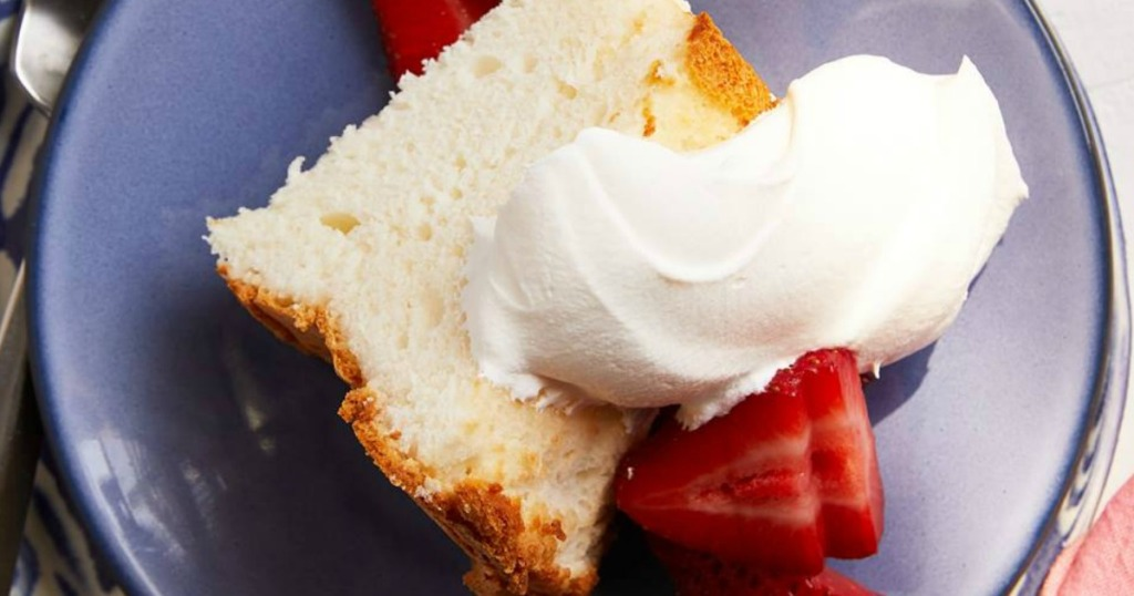 angel food cake slice on plate with whipped cream and strawberries