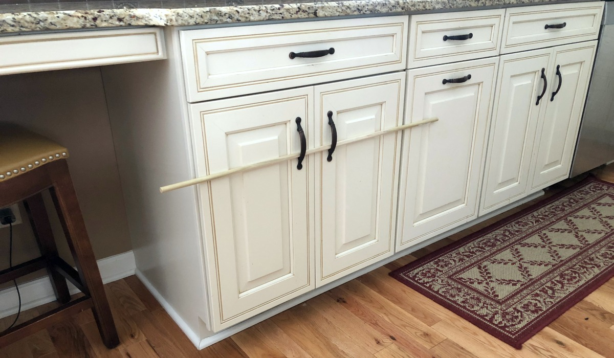 use wooden dowels to stop cabinets from opening